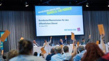 Teilnehmer halten Abstimmungskarten hoch, im Hintergrund Bühne mit Rednern